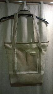 Rankinė. Telpa A4. Pagrindinis skyrius užsegamas užtrauktuku. Išorės priekyje ir nugaroje po kišenę. Viduje užsegama kišenėlė. Džiutas. Oda.